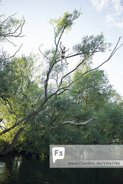 Teenage girl jumping from tree
