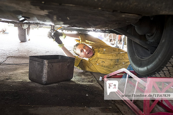 Woman mechanic repairing vintage car
