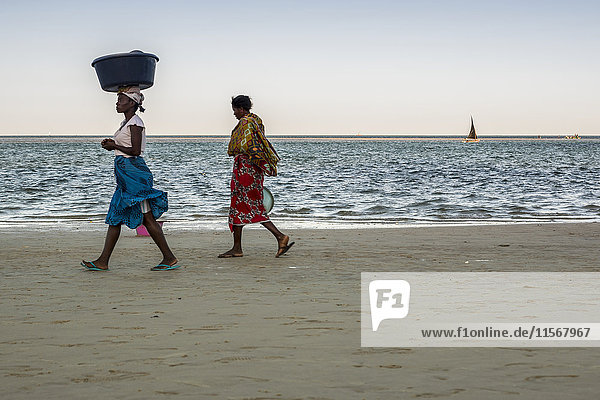 'Local women waiting for the fishermen arriving on their Dhows  Vilanculos beach; Bazaruto Archipelago  Mozambique'