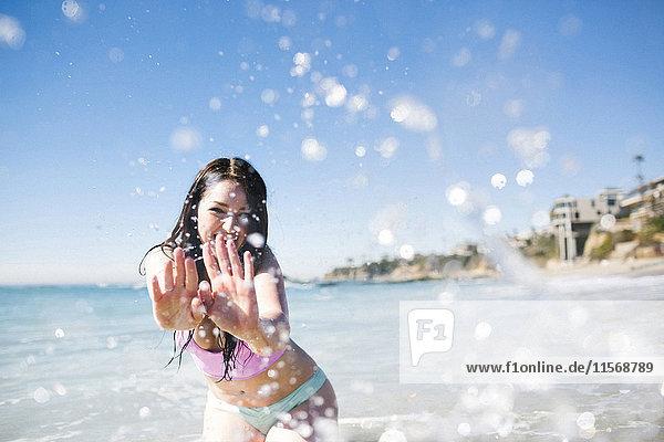 USA  California  Woman playing in water on Laguna Beach
