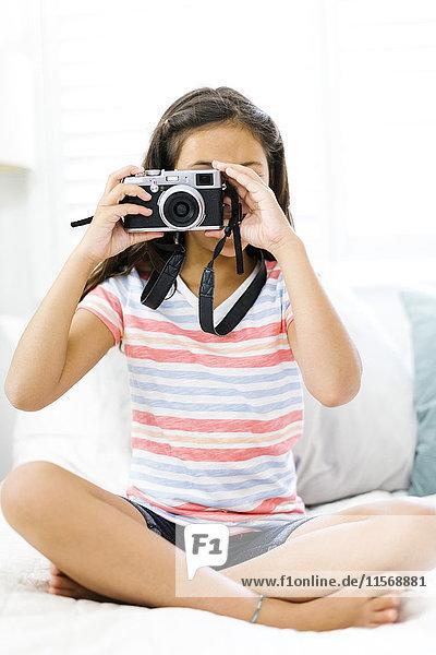Sitting girl (10-11) holding camera and taking photo