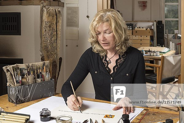 Calligraphy studio  woman writes text with pen and nib  Seebruck  Upper Bavaria  Germany  Europe