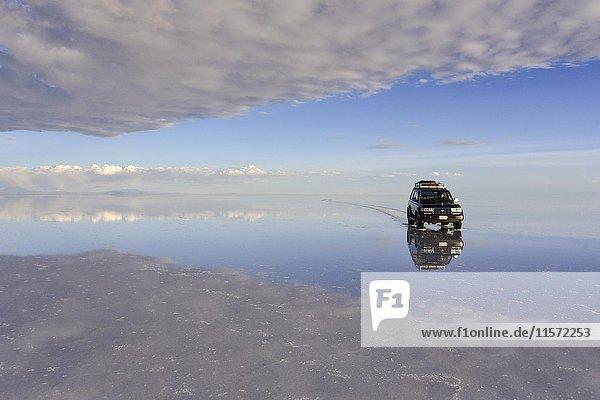 All terrain vehicle driving on a lake  water flooded salt lake  Salar de Uyuni  Altiplano  Bolivia  South America