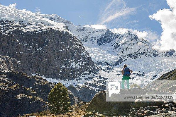 Wanderin steht auf Felsen  Ausblick auf Rob Roy Gletscher  Mount Aspiring National Park  Otago  Südinsel  Neuseeland  Ozeanien