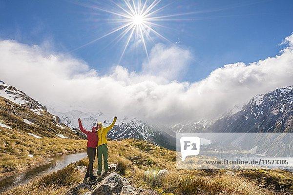 Zwei Wanderer strecken ihre Arme in die Luft  Ausblick in das Hooker Valley  Bergsee Sealy Tarns  Mount Cook Nationalpark  Canterbury  Südinsel  Neuseeland  Ozeanien