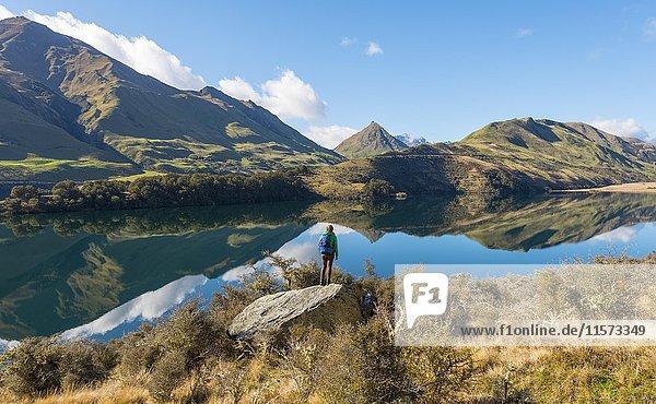Wanderin steht auf Felsen  Berge spiegeln sich im See  Moke Lake bei Queenstown  Otago  Südinsel  Neuseeland  Ozeanien