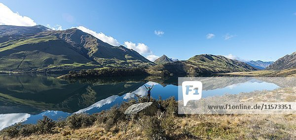 Wanderin steht auf Felsen und streckt die Arme in die Luft  Berge spiegeln sich im See  Moke Lake bei Queenstown  Otago  Südinsel  Neuseeland  Ozeanien