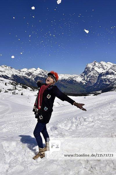 Asiatische Frau freut sich am Schnee in den Bergen  Kleine Scheidegg  Schweizer Alpen  Berner Oberland  Kanton Bern  Schweiz  Europa