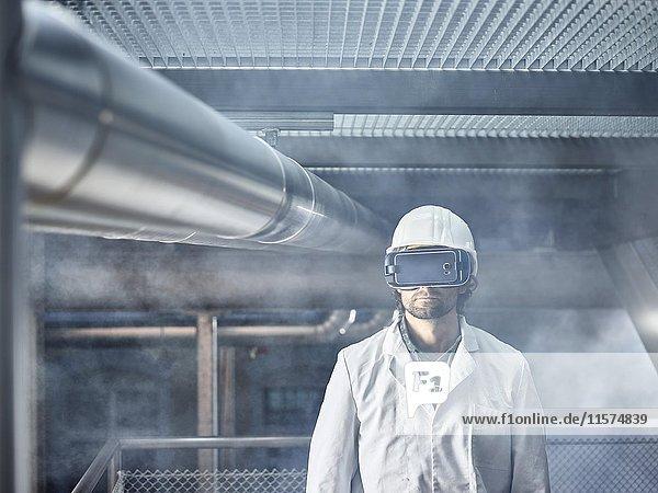 Mann mit VR Brille  weißen Helm und Labor Mantel steht vor Industrie-Anlage  Österreich  Europa