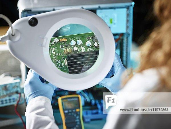 Technikerin mit weißem Labormantel überprüft eine Grafikkarte  schaut Platine durch Lupen an  Österreich  Europa