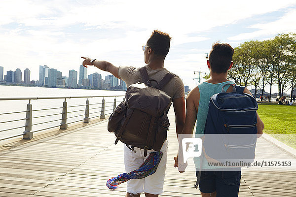 Young male couple strolling along East river waterfront  New York  USA