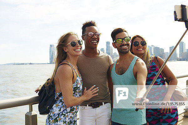 Four adult friends taking smartphone selfie on waterfront with skyline  New York  USA