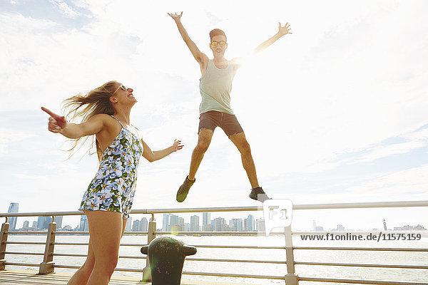 Junger Mann springt am sonnenbeschienenen Wasser in die Luft  New York  USA