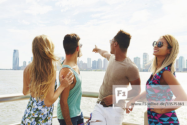 Four adult friends pointing at skyline from waterfront  New York  USA