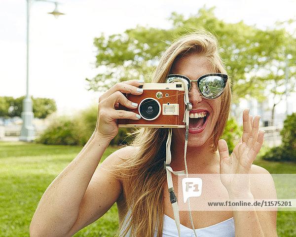 Porträt einer jungen Frau im Park  die mit einer Retro-Kamera fotografiert