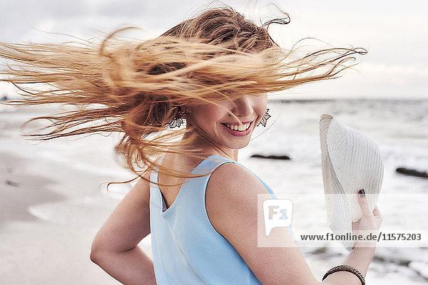 Frau schwingt Haare am Strand herum