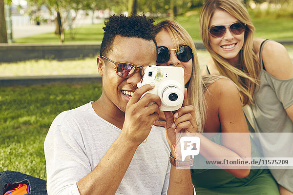 Young man and friends photographing with instant camera in park
