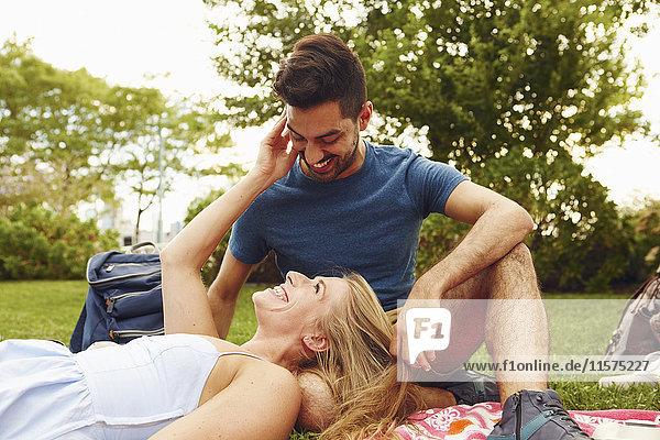 Junge Frau entspannt sich mit dem Kopf auf dem Schoß eines Freundes im Park
