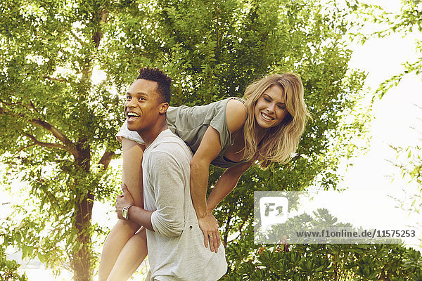 Young man carrying female friend over his shoulder in park