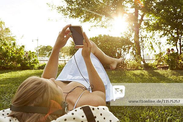 Junge Frau liegt im sonnenbeschienenen Park und wählt Smartphone-Musik