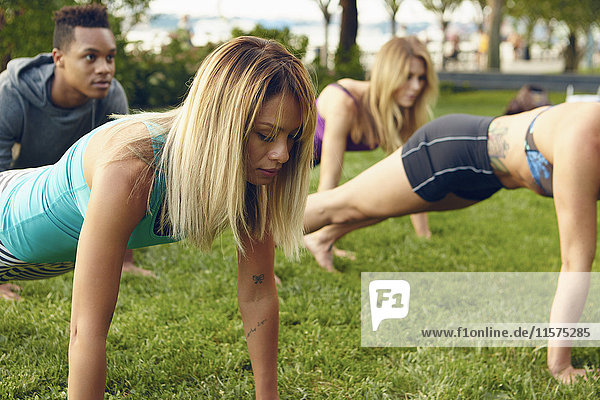 Male and female adults practicing yoga plank pose in park