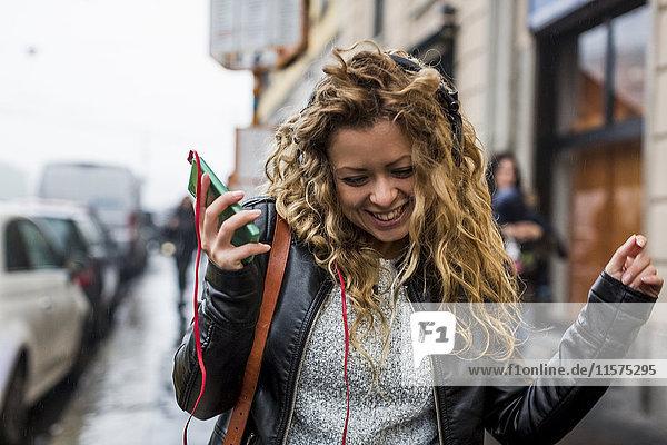 Woman in street listening to music through headphones