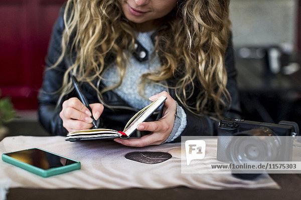 Frau im Café schreibt in Notizbuch