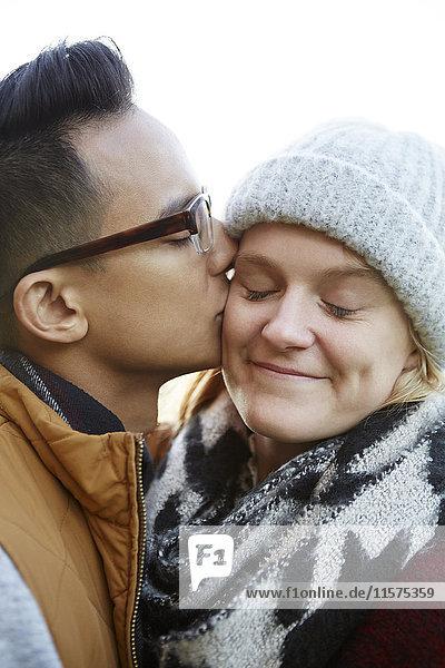 Close up of man kissing girlfriend's cheek