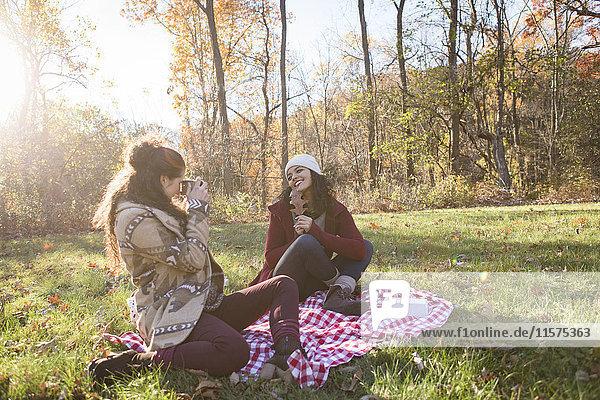 Junge Frau auf Picknickdecke fotografiert Freund