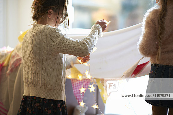 Two sisters in bedroom den hanging bunting and star shape lights