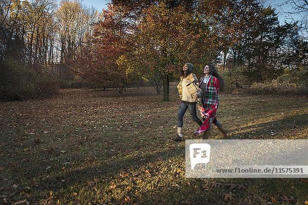 Zwei Freundinnen schreiten durch den Herbstpark