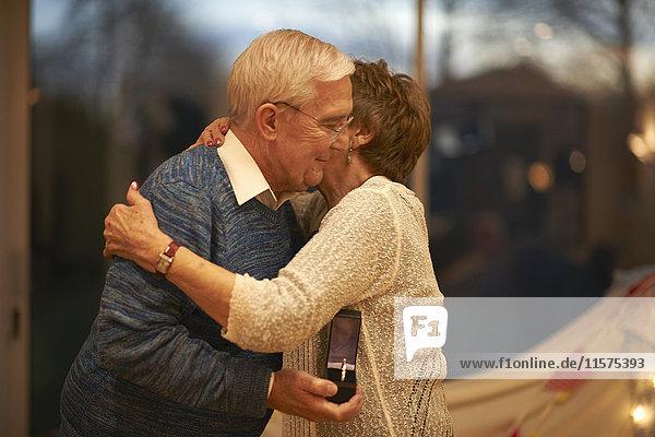 Romantic senior couple hugging while holding gift box
