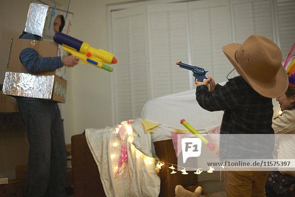 Senior man in robot costume shooting toy guns with dressed up grandchildren