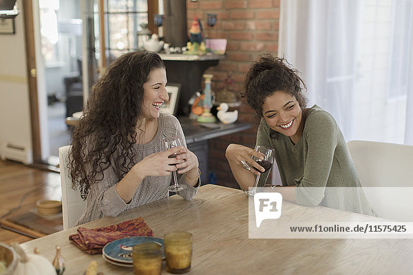 Two young women friends laughing at kitchen table
