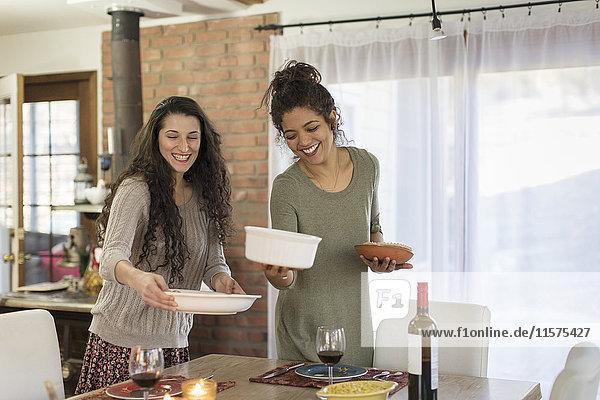 Zwei junge Freundinnen bereiten das Essen am Küchentisch vor