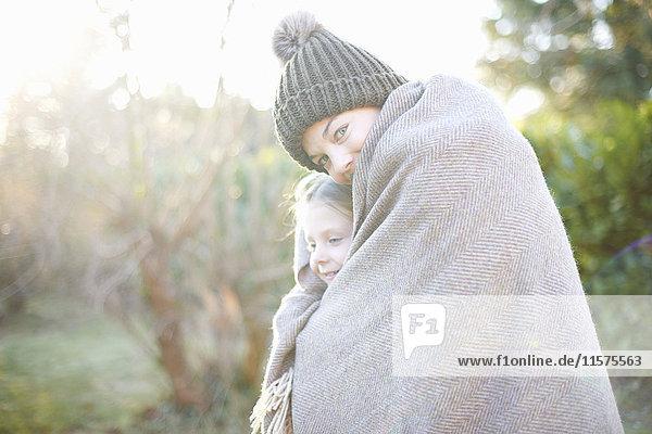 Siblings wrapped in blanket