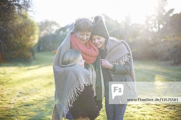 Grandmother and granddaughters hugging in garden