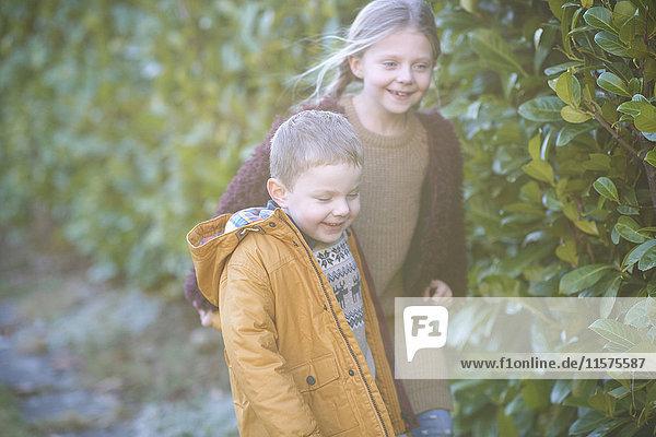 Siblings walking in garden