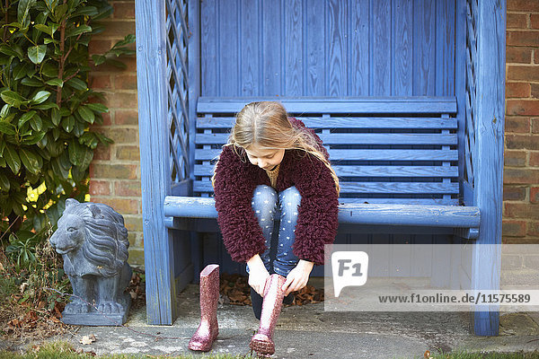Girl putting on boots on arbour bench