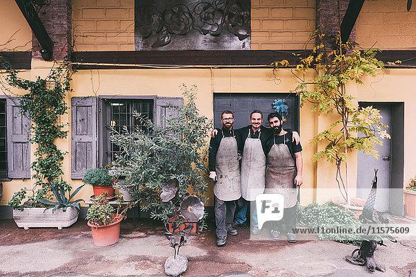 Porträt von drei Metallarbeitern außerhalb der Schmiede