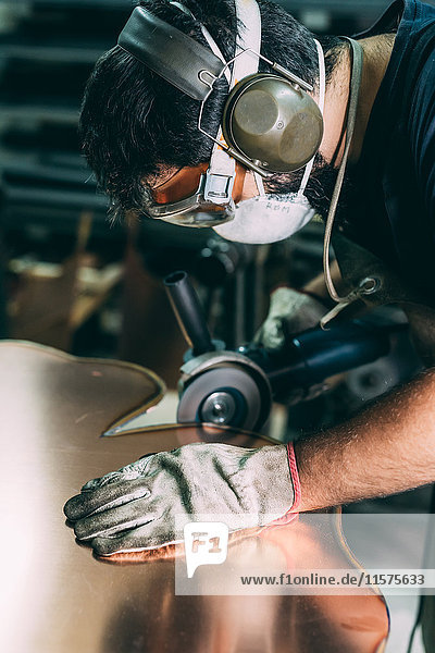 Metalworker grinding the edge of copper in forge workshop