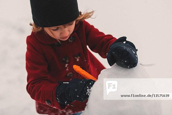 Mädchen benutzt Möhre als Schneemannnase