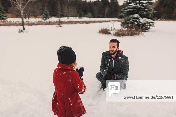 Mädchen wirft Schneeball auf ihren Vater