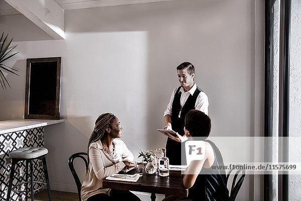 Kellner  der die Gäste im Restaurant bedient  wartet mit einem digitalen Tablett.