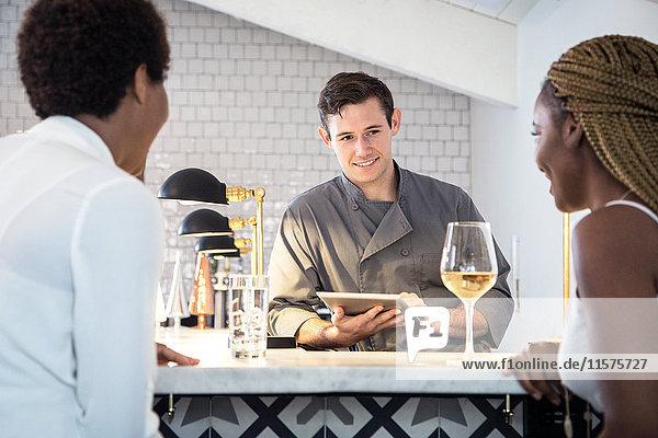 Barkeeper bedient Kunden an der Bar  Barkeeper mit digitalem Tablett
