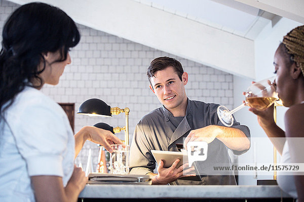 Barkeeper bedient Kunden an der Bar  Barkeeper nutzt digitales Tablett zur Zahlungsannahme