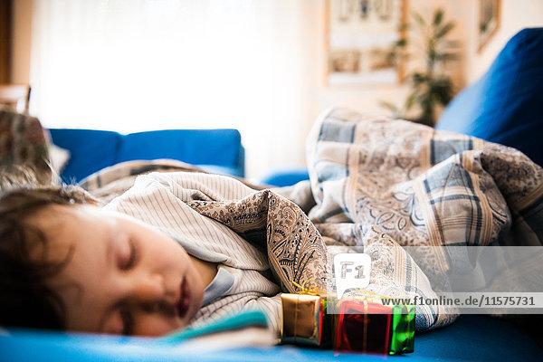 Baby boy sleeping on sofa in blanket