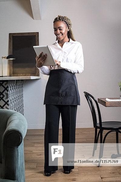Porträt eines Kellners in einem Restaurant  der ein digitales Tablett benutzt