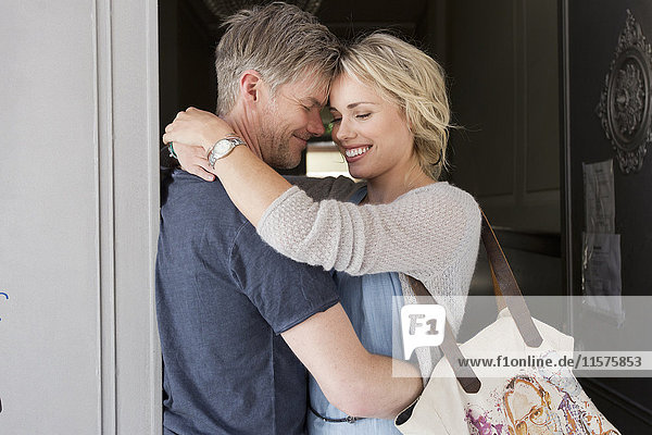 Couple hugging face to face in doorway