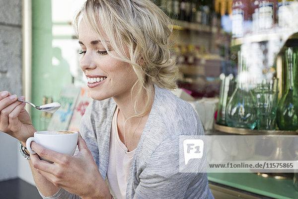 Mittelgroße erwachsene Frau isst Schaum aus Kaffeetasse im städtischen Straßencafé